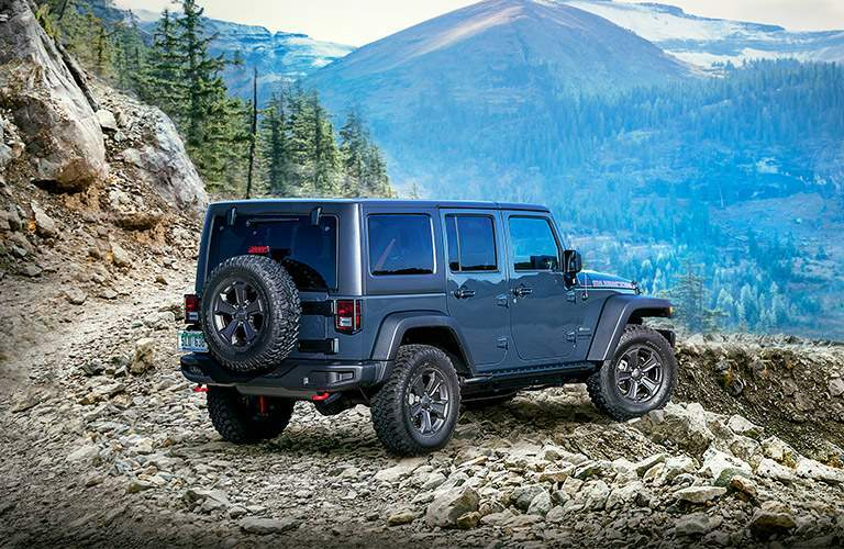 rear of 2018 jeep wrangler jk rubicon shown facing mountain on rocky hillside
