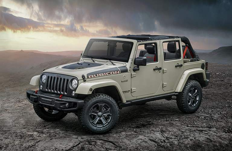 2018 jeep wrangler jk rubicon unlimited shown in tan on rocky cliff hill from front exterior
