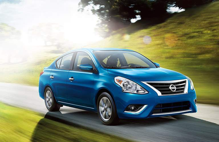Front quarter profile of the 2018 Nissan Versa driving by a grassy hill