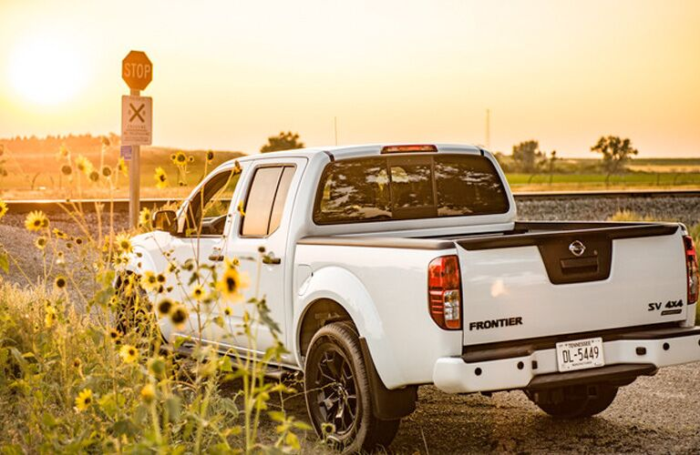 2019 Nissan Frontier parked before a train track and admiring the setting sun behind distant grassy hills. Exterior rear angled view.