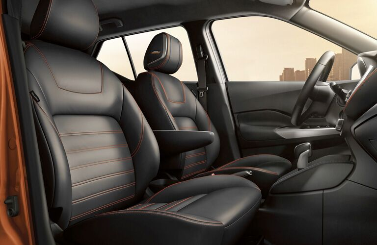 Interior front row of a 2019 Nissan Kicks, showcasing the comfortable seats with stylish orange stitching.