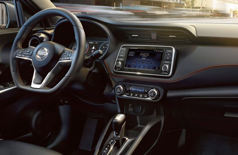 Interior cabin view of the infotainment, steering wheel, and visibility from inside a 2019 Nissan Kicks.