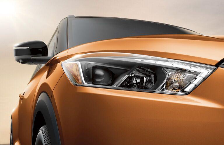 Close up of the passenger side headlight on an orange 2019 Nissan Kicks