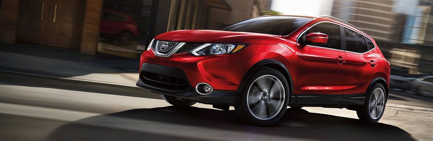 Red 2019 Nissan Rogue Sport cruises down a city street.