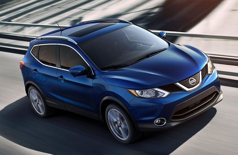 Blue 2019 Nissan Rogue Sport drives down a highway. Exterior front/side above-angled view.