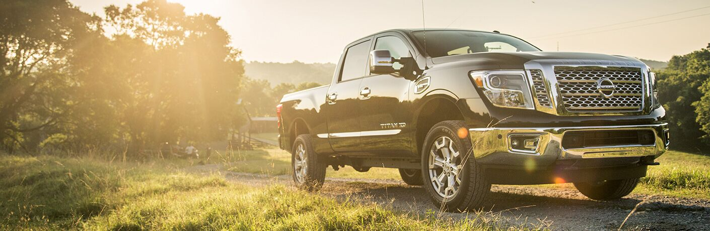 2019 Nissan TITAN exterior side-angled front view. Parked out in sunny green field amongst bunches of trees.