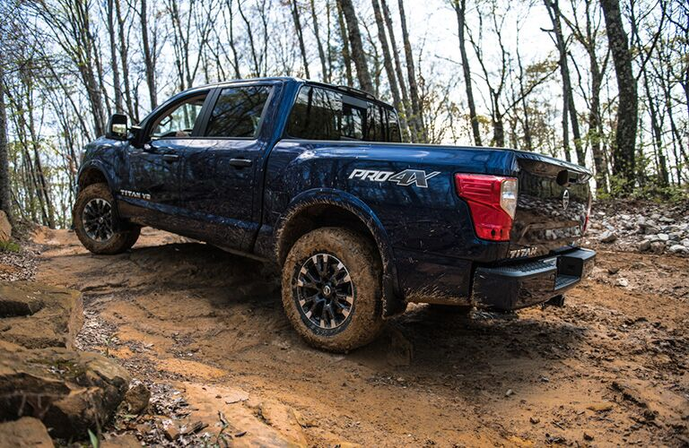 A 2019 Nissan TITAN clambers over some rough terrain in the woods. Exterior side-angled rear view.