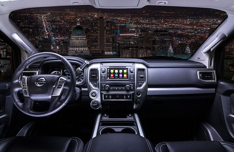 Interior front view of a 2019 Nissan TITAN showcasing the dashboard and infotainment. View of an illuminated city at night.