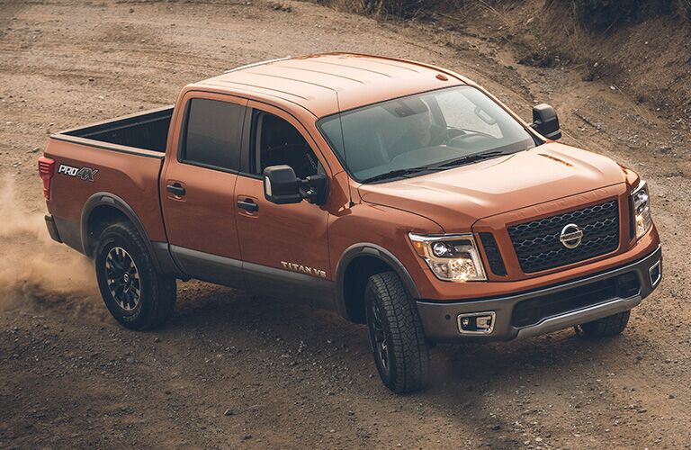 2019 Nissan TITAN drives through a sandy environment. Raised exterior front angled view.