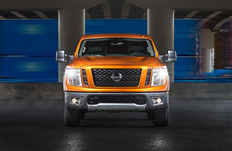 Orange 2019 Nissan Titan parked in a garage. We see it from a head-on view as it shines its headlights in our face.