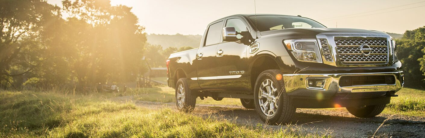 A 2019 Nissan Titan XD sits in a field of green grass as golden sun beams down upon it.