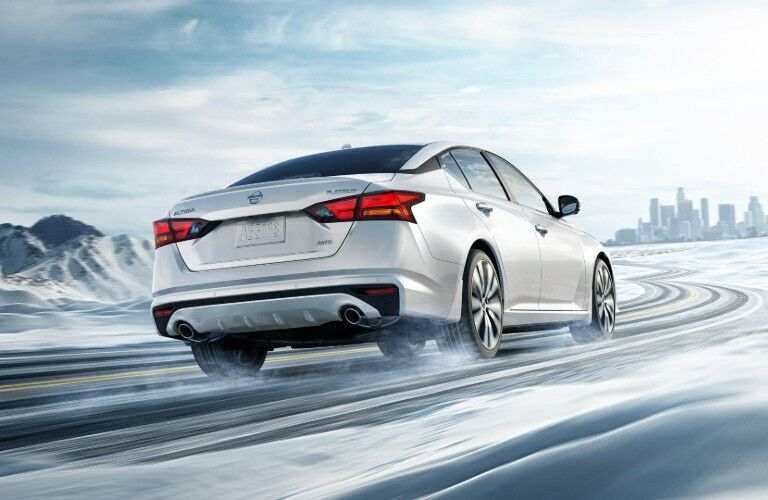Rear passenger angle of a white 2020 Nissan Altima driving on a snowy road