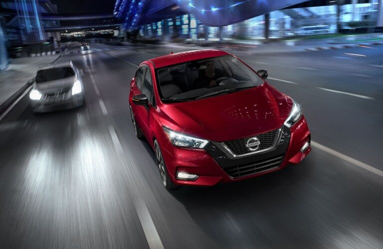 Front passenger aerial angle of a red 2020 Nissan Versa sedan driving on a road with another vehicle behind in another lane