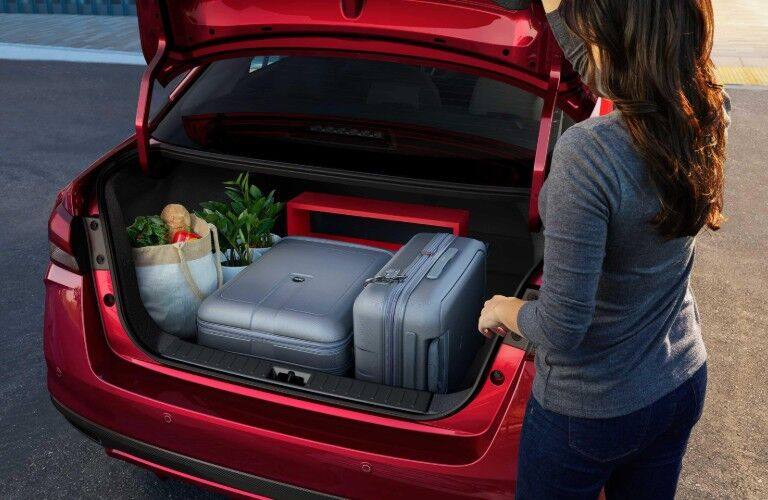 Woman by the trunk of a red 2020 Nissan Versa with luggage and groceries inside