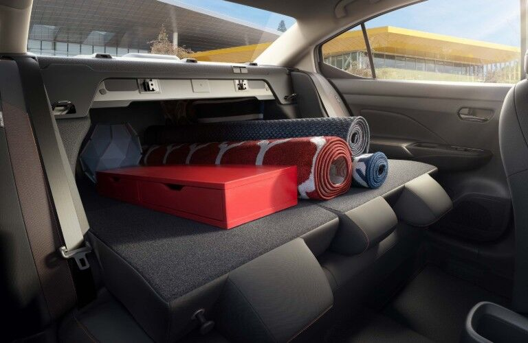 Back seats put down with long items from trunk coming out in the 2020 Nissan Versa sedan