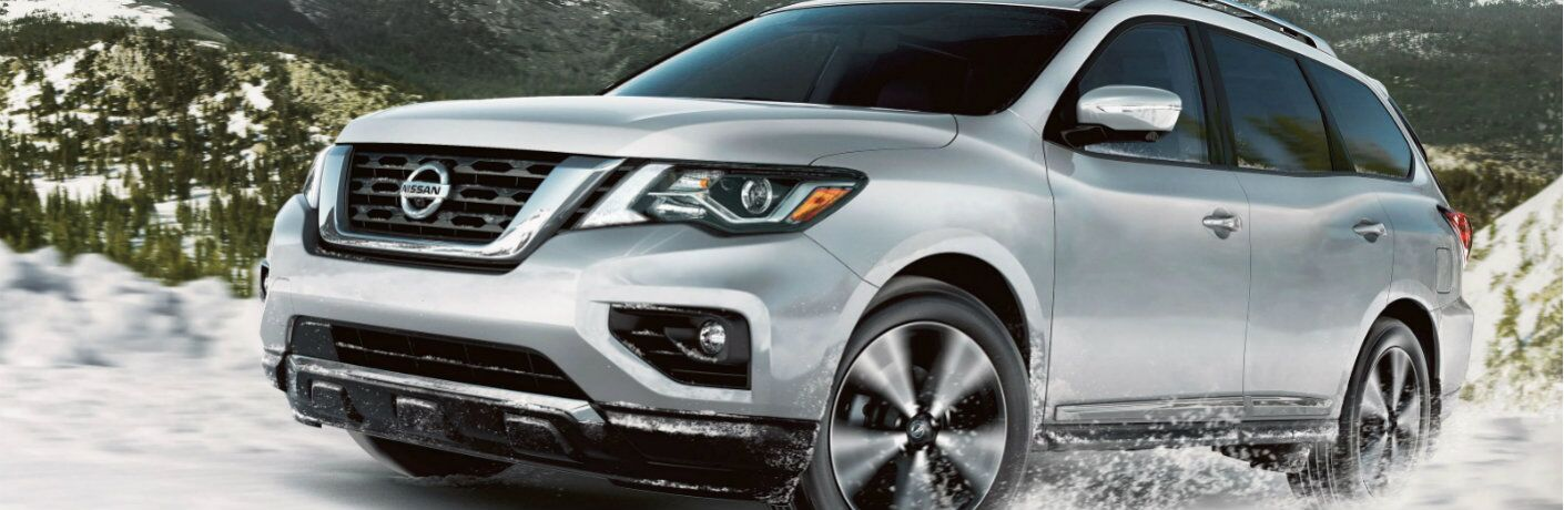 2020 Nissan Pathfinder driving through snow and mountains