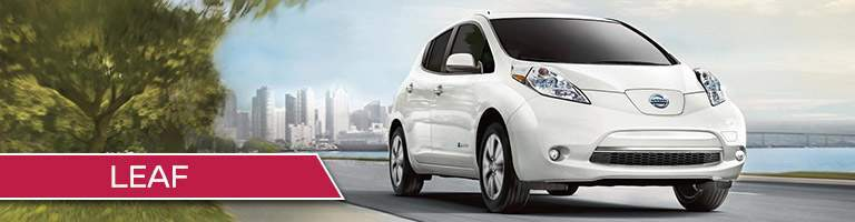 White Nissan Leaf driving down lakefront road with trees and city skyline in background