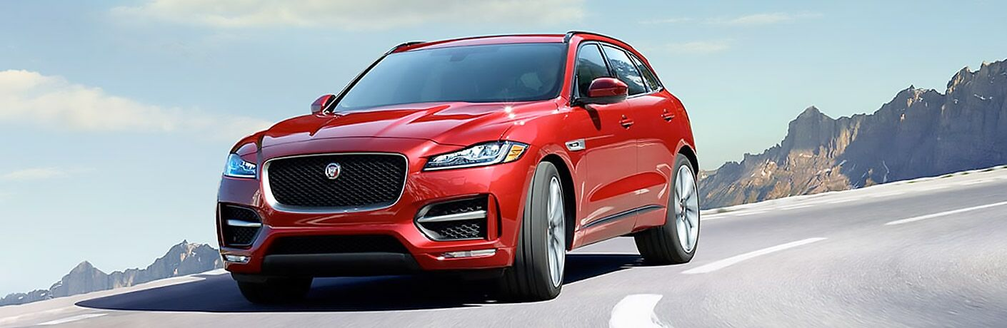 front view of an orange-red 2018 Jaguar F-PACE driving on a curved road