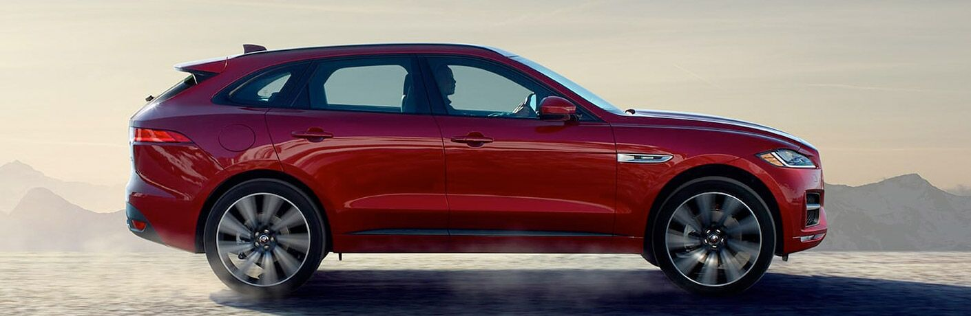 profile of a red 2018 Jaguar F-PACE on the road driving