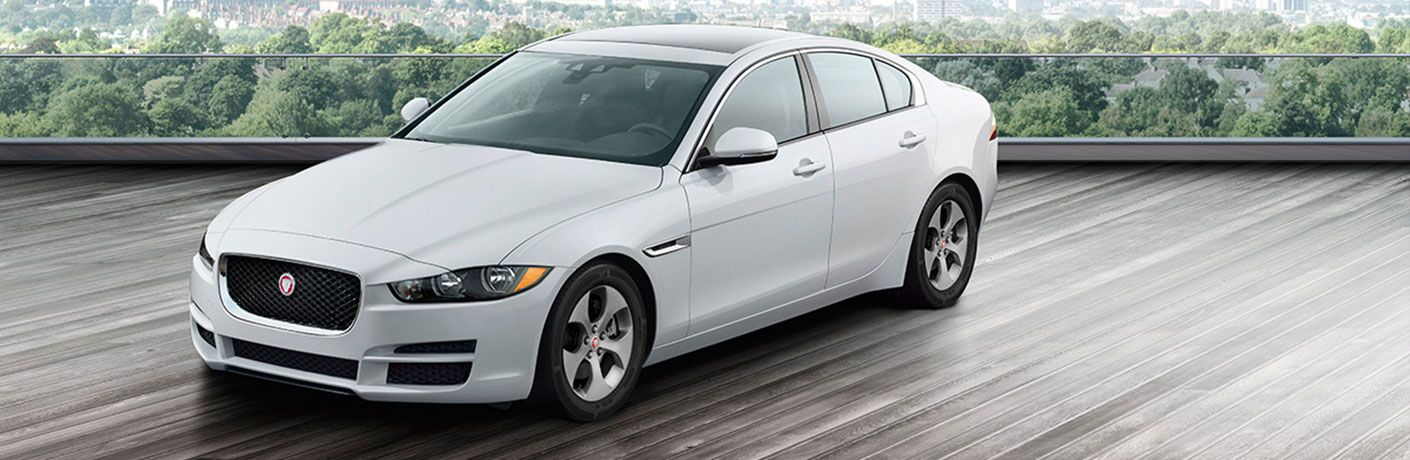 White 2018 Jaguar XE parked on tree-lined driveway