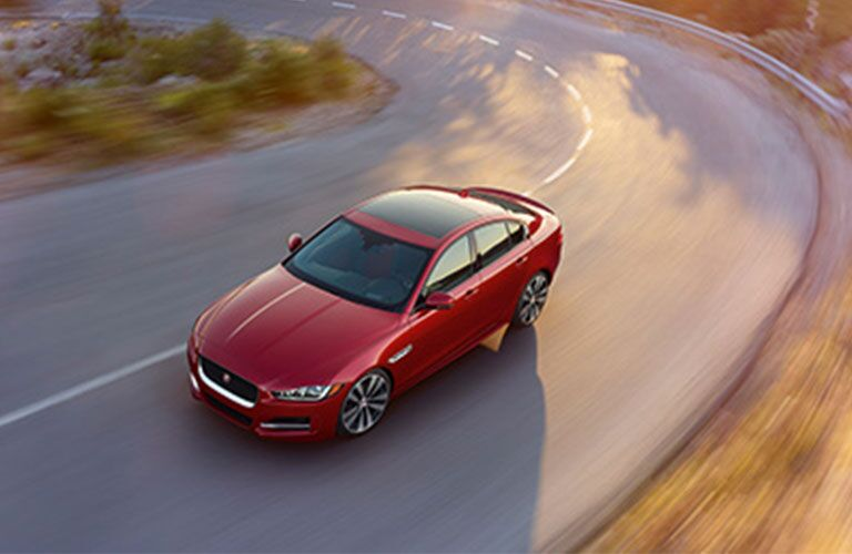 Overhead view of red 2018 Jaguar XE driving on curved road
