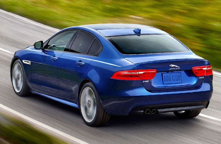 Rear view of blue 2018 Jaguar XE driving on country road