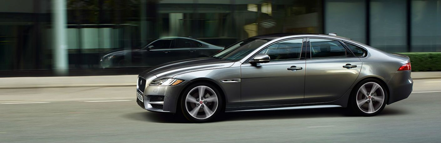 Profile view of Jaguar XF driving in front of city building