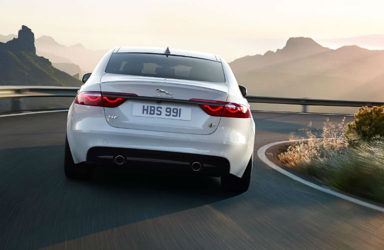 Jaguar XF driving on winding road with mountains in background