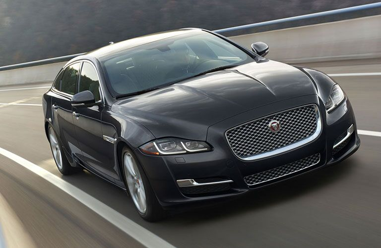 Front view of black 2018 Jaguar XJ driving on highway road