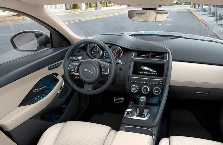 Interior view of the black steering wheel and dashboard with touchscreen infotainment system of a 2019 Jaguar E-PACE