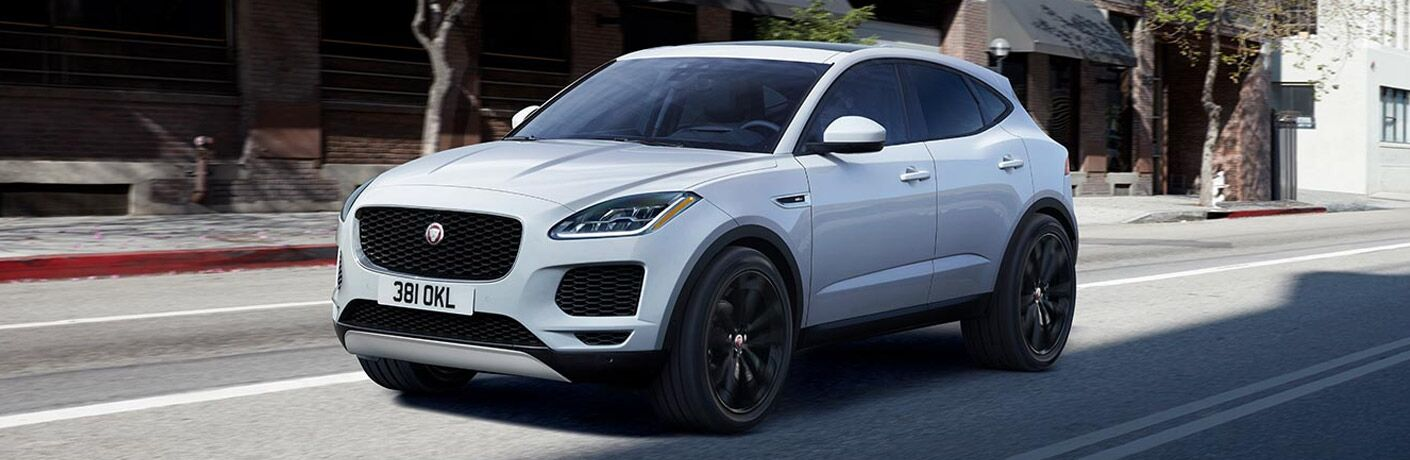 Exterior view of a white 2019 Jaguar E-PACE driving down a city street during the day