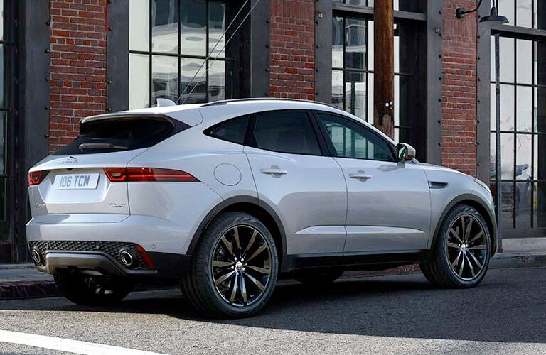 Exterior view of the passenger's side of a white 2019 Jaguar E-PACE parked outside of a brick building during the day