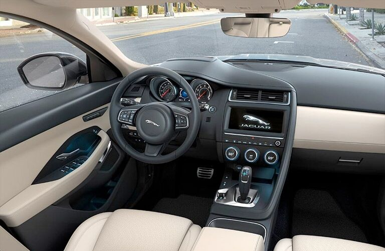 Interior view of the tan seating, black steering wheel, and touchscreen inside a 2019 Jaguar E-PACE