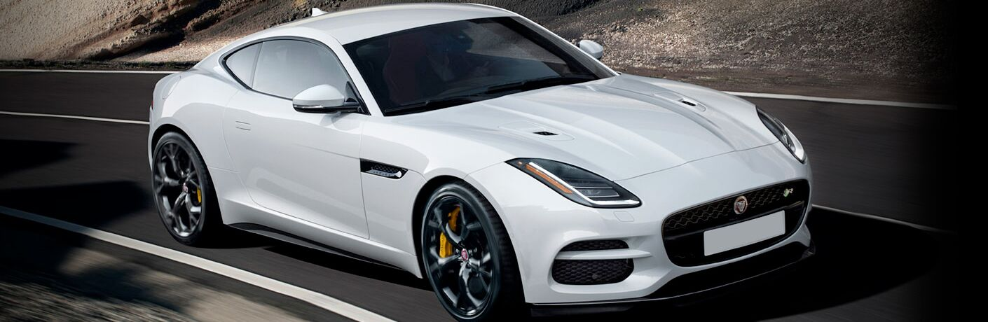 Long view of white 2019 Jaguar F-TYPE driving on mountain road