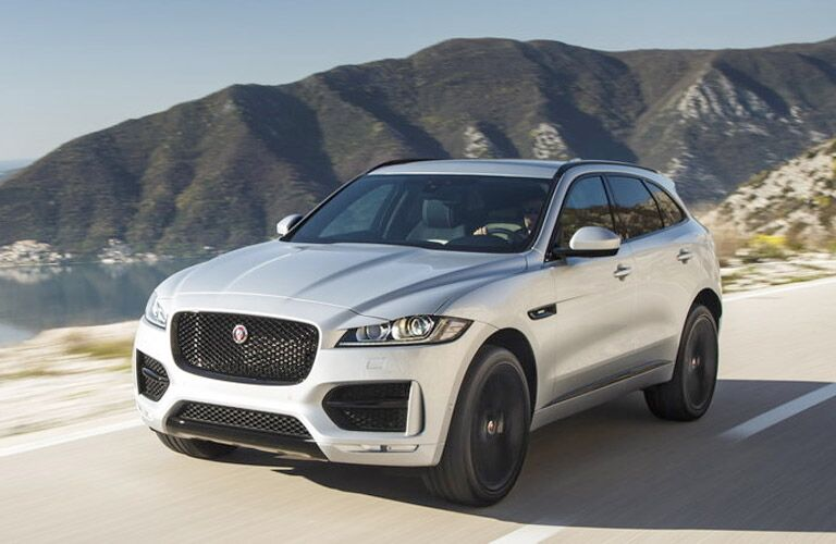 Exterior view of the front of a silver 2019 Jaguar F-PACE driving down a road with mountains in the background