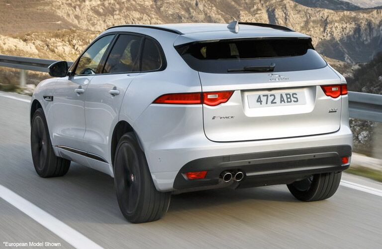 Exterior view of the rear of a silver 2019 Jaguar F-PACE driving down a mountain-side road