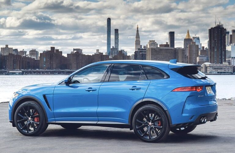 Exterior view of a blue 2019 Jaguar F-PACE parked next to a river in the city with skyscrapers in the background