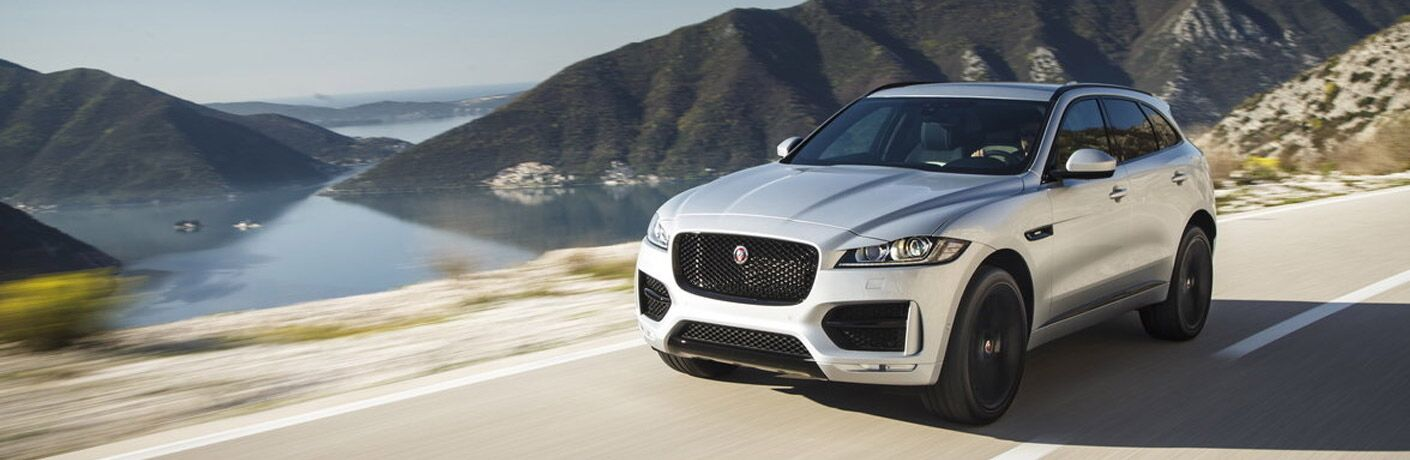 Featured image of a silver 2019 Jaguar F-PACE driving down a highway with mountains and body of water in the background