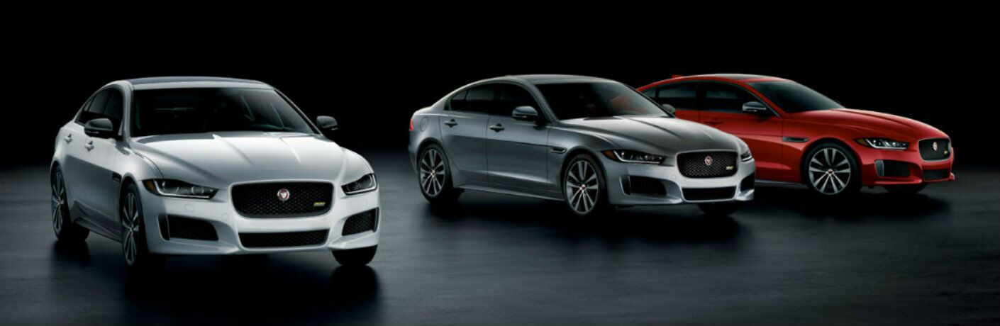 Exterior view of three different 2019 Jaguar XE models in a dark showroom