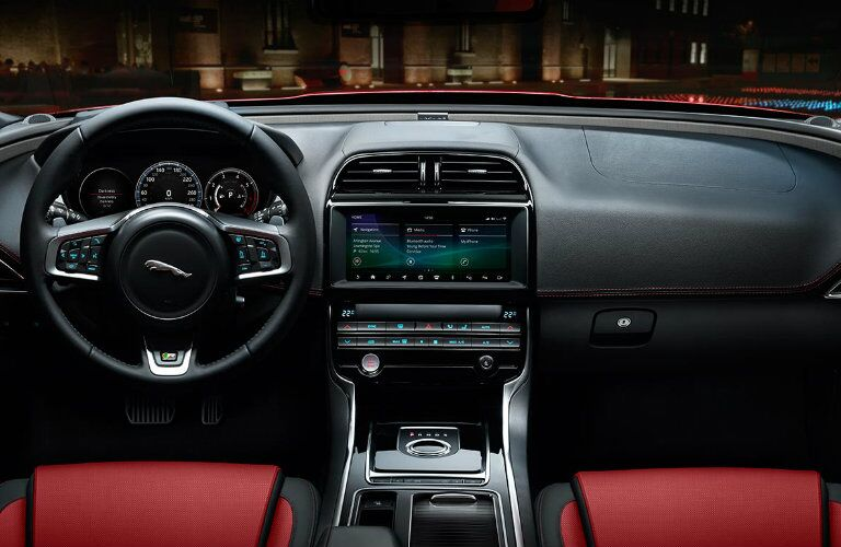 Interior view of the black steering wheel and touchscreen of a 2019 Jaguar XE
