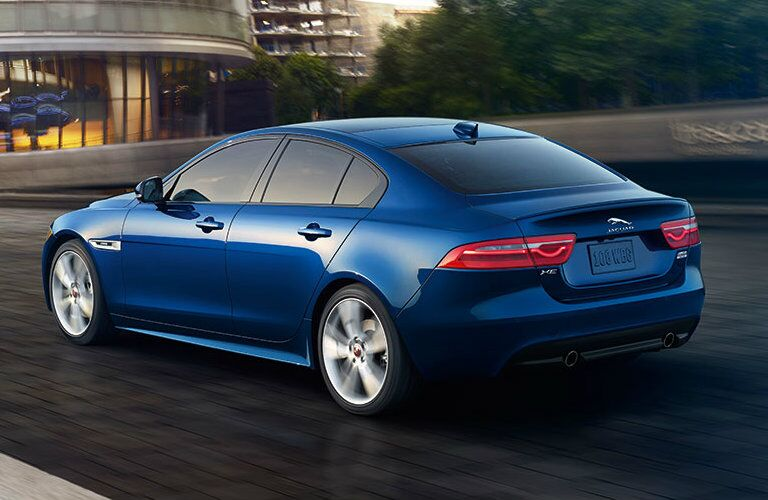 Exterior view of the rear of a blue 2019 Jaguar XE driving down the highway