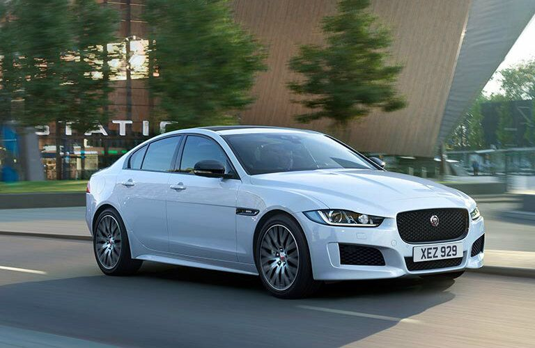 Exterior view of the front of a white 2019 Jaguar XE driving down a city street