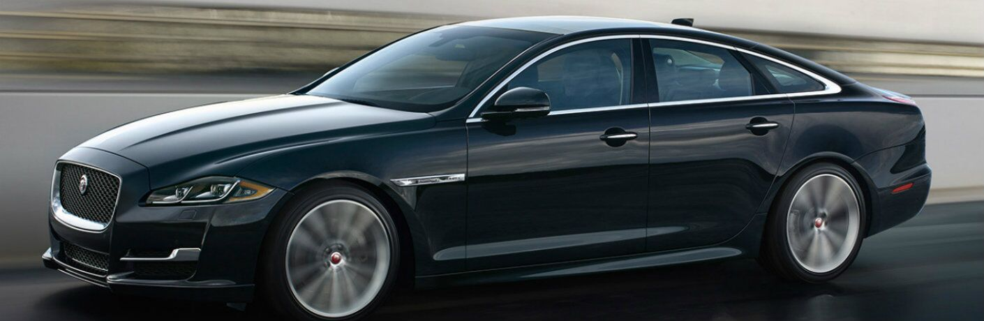Exterior view of a black 2019 Jaguar XJ driving down a wet highway