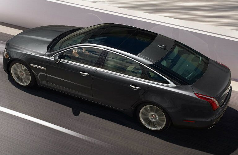 Exterior elevated view of a black 2019 Jaguar XJ driving down a highway