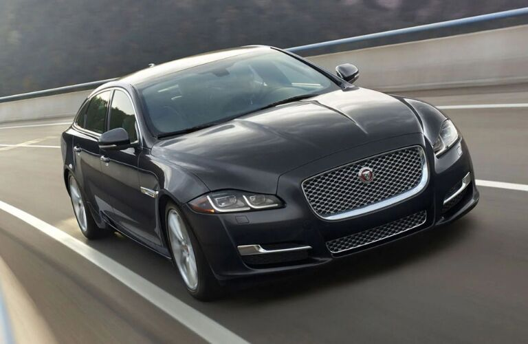Exterior view of the front of a black 2019 Jaguar XJ driving down the highway