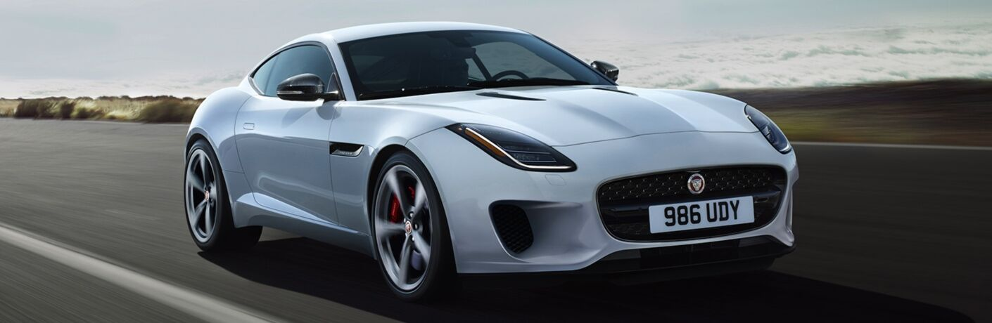 Exterior view of a white 2020 Jaguar F-TYPE driving down a desert road