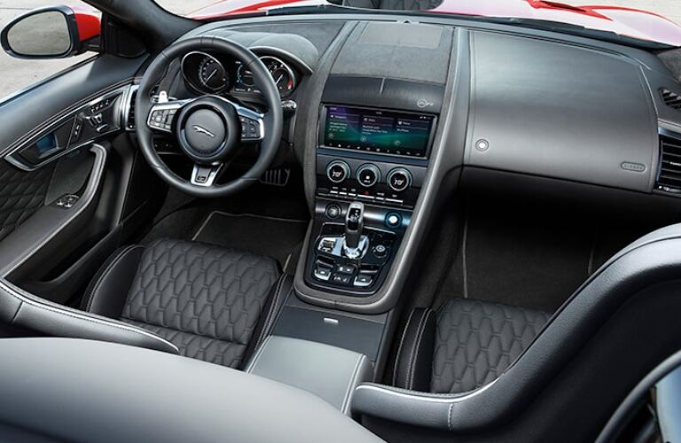 Exterior view of the steering wheel and front seating area inside a 2020 Jaguar F-TYPE