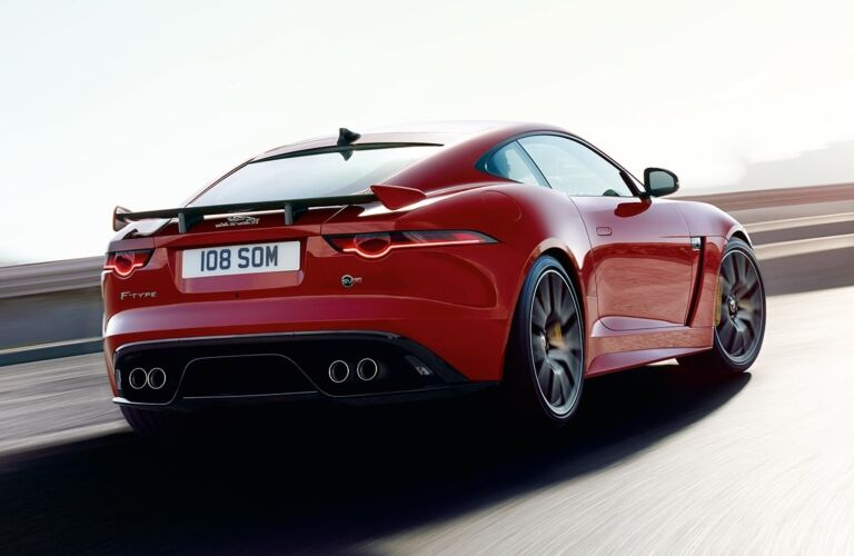Exterior view of the rear of a red 2020 Jaguar F-TYPE dirivng down an empty racetrack
