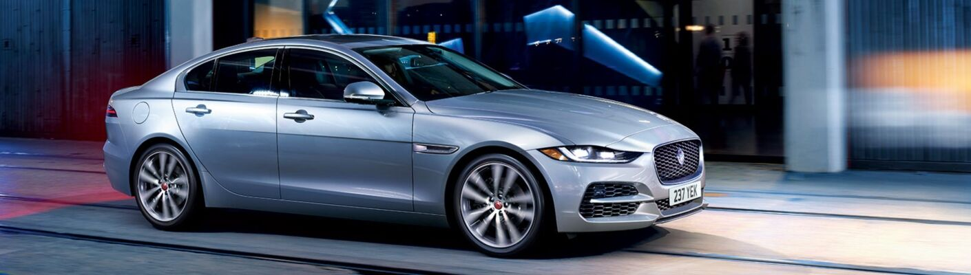 Exterior view of a silver 2020 Jaguar XE driving down a city street