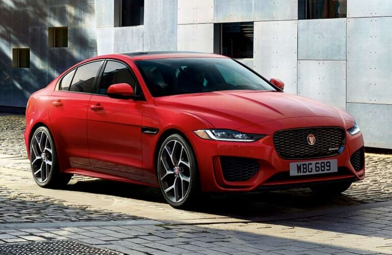 Exterior view of the front of a red 2020 Jaguar XE parked on a brick road